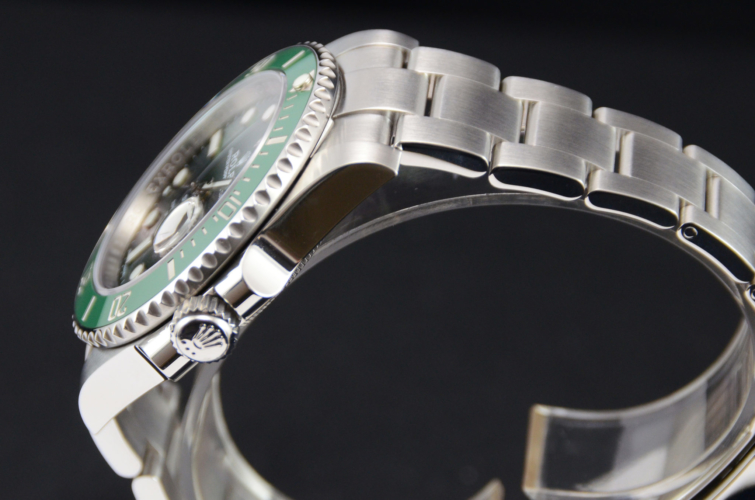 """Detail view image of a stainless steel Rolex Submariner Date 116610LV """"Hulk"""" with a green sunburst effect dial and green bezel"""
